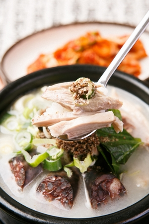 Spoon scooping up korean sausages soup in black pot Banque d'images