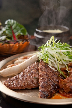 Short rib patties, sausages, seasoned green onions being grilled on grill