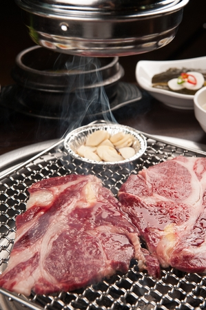 Beef sirloin and garlic being grilled on charcoal grate