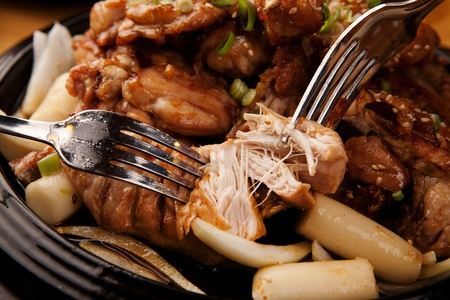 Fork tearing apart Soy sauce barbecue chicken with onions and rice cakes, on black oven plate Foto de archivo