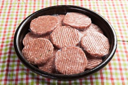 Short rib patties packaged in vinyl on black plate