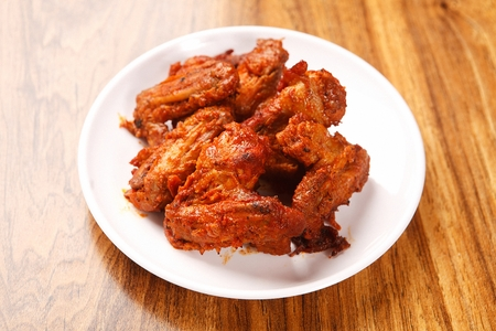 Spicy marinated chicken wings on round plate