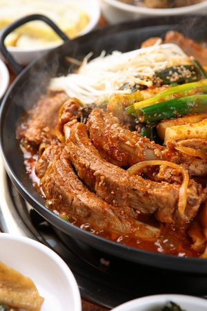 Braised pork back ribs with ripened kimchi, in black stew pot