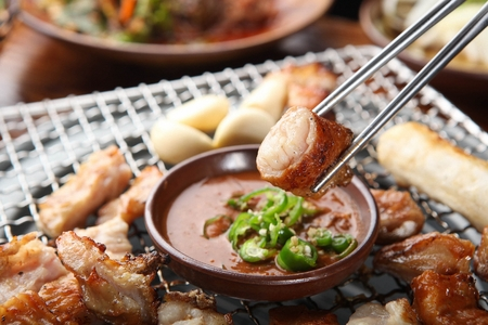 Chopsticks dipping pork entrails being grilled on charcoal grate into sauce Stock fotó