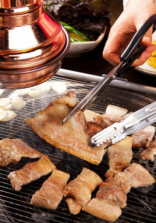 Scissors cutting pork belly being grilled on charcoal grate Stockfoto