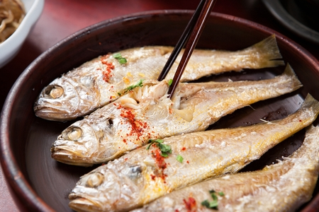 Chopsticks picking up grilled yellow croaker with sprinkled chili powder and chives, on round plate Stockfoto - 115588834