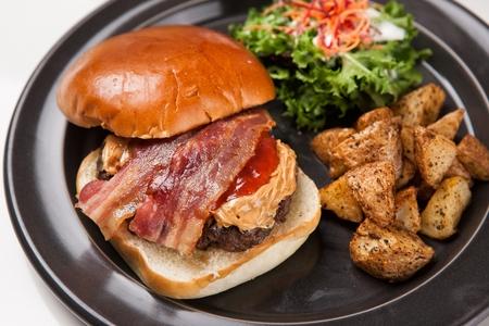 Hamburger, french fries, salad on round plate Banco de Imagens