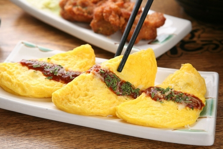 Chopsticks picking up Omelette with sprinkled sauce and parsley powder on rectangular plate Foto de archivo