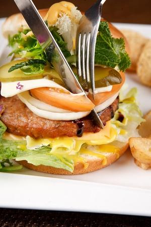 Knife cutting a hamburger with hamburg steak, tomato and onions, on rectanguar plate