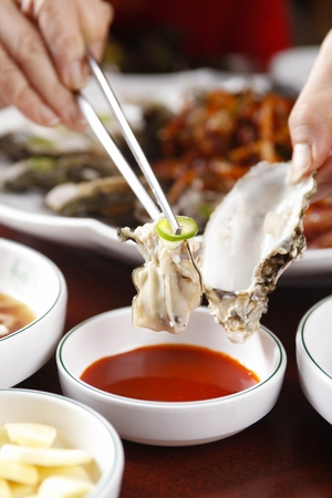 Chopsticks dipping raw oysters in sauce, on round plate