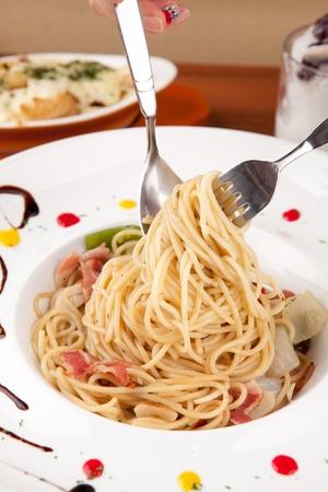 Fork rolling aglio e olio on spoon