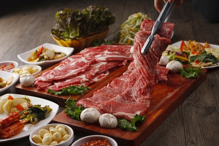 Pincers picking up beef sirloin from wooden cutting board Stockfoto