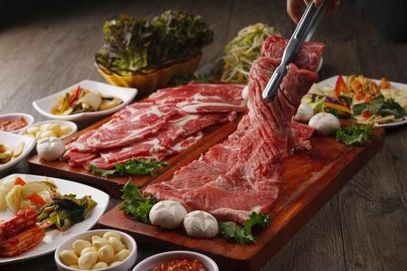 Pincers picking up beef sirloin from wooden cutting board Standard-Bild