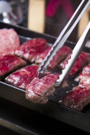 Pincers picking up beef sirloin being grilled on black grill
