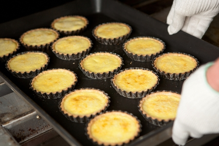 Chef's gloved hand getting freshly baked egg tarts from the oven