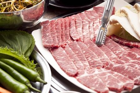 Pincers picking up beef brisket on rectangular plate