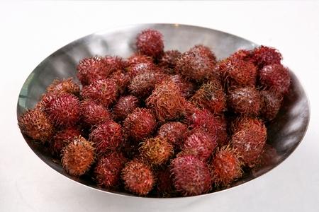 Tropical fruit rambutan, on round silver plate