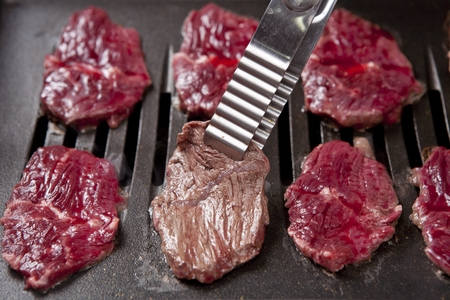 Pincers picking up beef spleen meat being grilled on charcoal grill Stockfoto