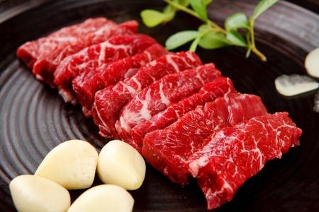 Beef chuck flap tail and whole garlic on round plate Zdjęcie Seryjne