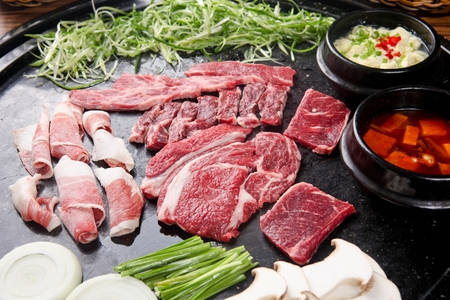 Beef sirloin, beef brisket, beef spleen meat, steamed eggs, onions, chives, king oyster mushrooms being grilled on black grill Stockfoto