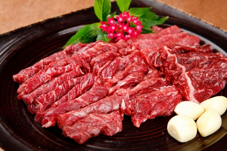 Beef spleen meat and whole garlic on rectangular plate