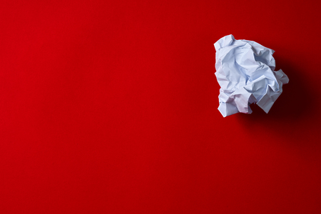 Crumpled paper ball on red background