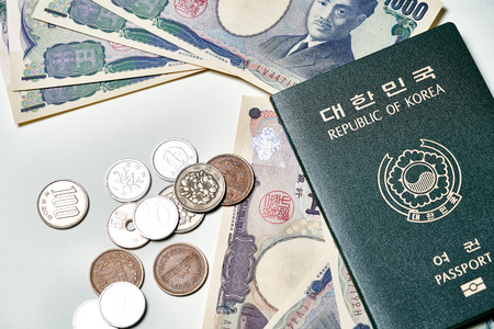 Closeup of Japanese Yen banknotes and Japanese Yen coin with Korean passport