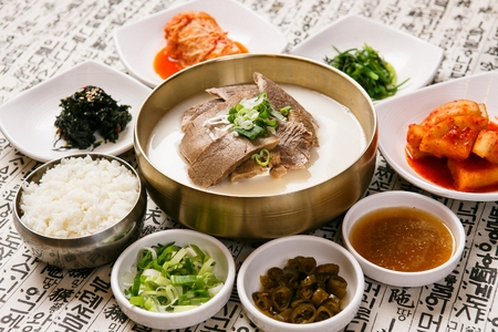 Ox bone soup with lots of meat, on bowl, served with side dishes on a table with a background containing Chinese characters Zdjęcie Seryjne