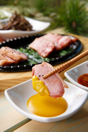 Chopsticks dipping chives and pork belly from iron plate in mustard