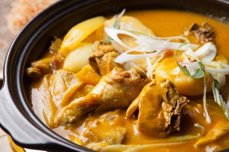Curry braised chicken with onions and seasoned green onions, in pot