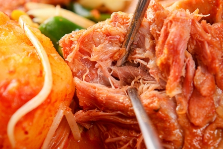Chopsticks tearing apart meat from braised back ribs with potatoes, onions and seasoned green onions, in pot