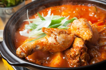 Braised spicy chicken with potatoes, rice cakes and onions, in pot Imagens