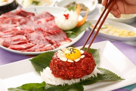 Chopsticks picking up beef tartare with egg yolk, on white plate 版權商用圖片