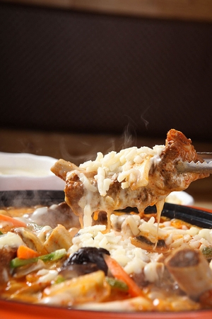 Pincers picking up meat from braised back ribs with carrots, mushrooms and cheese, in pot