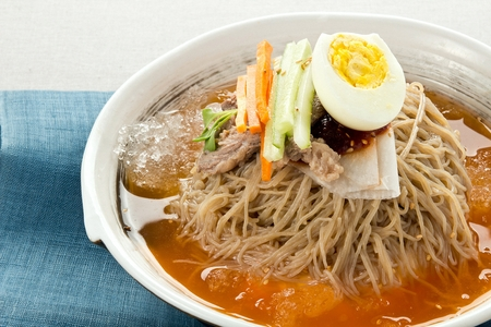 Cold buckwheat noodles soup with cucumber and eggs garnish, in bowl 版權商用圖片