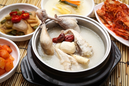 Chicken soup with chestnuts, ginseng, jujube in pot, with side dishes 写真素材