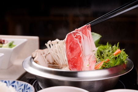 Chopsticks picking up meat from shabu-shabu made of various vegetables such as mushrooms and pak choi, with glass noodles, in pot