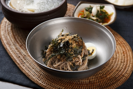 Buckwheat noodles soup with dried seaweed and eggs garnish, in bowl 스톡 콘텐츠