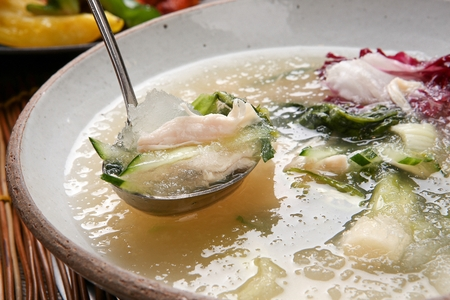Ladle scooping up cold noodles with cucumber, young radish and chicken meat, in bowl