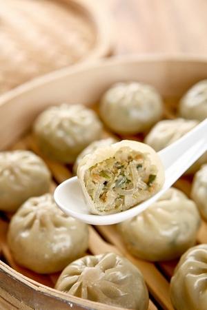 Spoon scooping up steamed dumplings from steamer