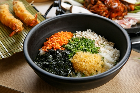 Ingredients for stir-fried rice such as carrots, mushrooms and dried seaweed on black plate