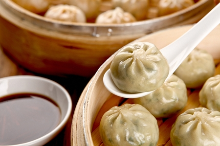 Spoon scooping up steamed dumplings from steamer, and soy sauce in small plate