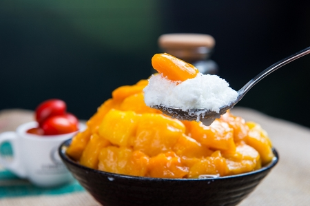 Spoon scooping up mango shaved ice with mangoes, in white bowl