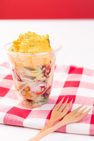 Vegetables salad with grinded sweet potatoes in plastic cup