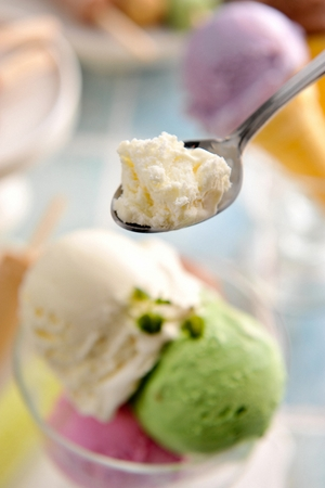 Spoon scooping up a scoop of ice cream in transparent bowl