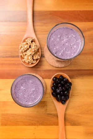 Smoothie made of grinded walnuts and blueberry in glass 免版税图像