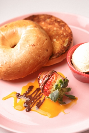 Baked bagel on pink plate, and one scoop of ice cream on plate 版權商用圖片