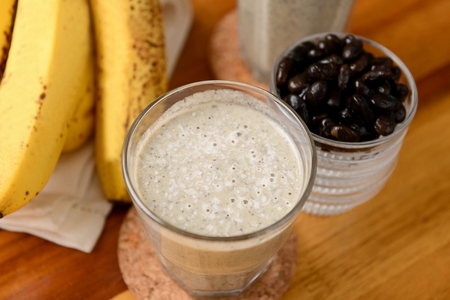 Smoothie made of grinded bananas and black beans in glass