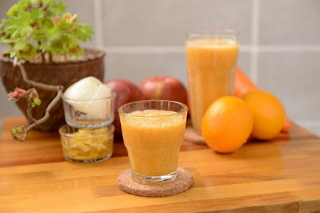 Smoothie made of grinded oranges and apples in glass