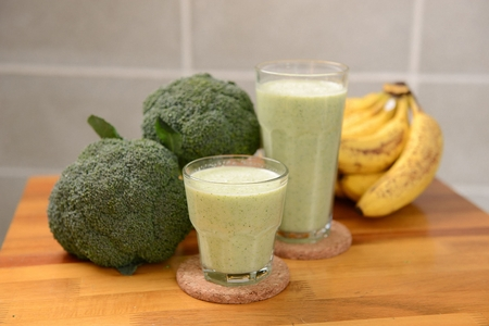 Smoothie made of grinded bananas and broccoli in glass